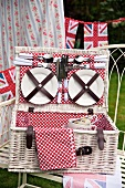 Plates and cutlery in the lid of an open, white picnic basket lined with red and white spotted fabric and stylised Union Jack bunting in the background