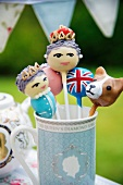 Close up of funny lollies decorated as the Queen, a Union Jack and a corgi in a British tea cup