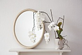 A white orchid and an oval mirror on a shelf