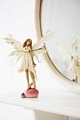 A fairy figurine in front of an oval mirror on a shelf