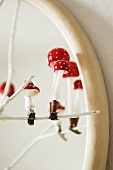 Glass toadstools on clips decorating a white-painted twig