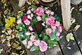 Wreath of roses and fallen autumn leaves on garden table