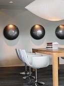 weiße Designerstühle an massivem Holztisch auf dunklem Parkettboden, an der weißen Wand angestrahlte Metallhalbkugeln
