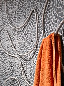 Curved shower hose mounted on pebble mosaic tiled wall and used as towel rail for orange towel