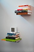 Stacks of books hanging on white wall on invisible brackets