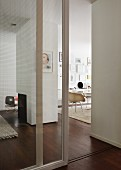 Open glass door element leading to modern, open-plan interior with central fireplace and dark parquet floor uniting the living areas