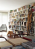Large bookcase with white shelves, wooden sculpture leaning on bookcase, books on table in foreground, modern reading chair in background