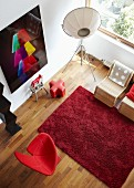 View down into living room with red rug, designer armchair, designer standard lamp and photographic artwork