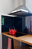 Corner of modern kitchen with reflective, black cupboard doors and red kettle on black ceramic hob