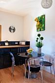 Kleiner, runder Esstisch mit Plexiglasstühlen in moderner Küche mit schwarzer Küchenzeile und hellem Parkettboden