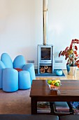 Pastel blue log burner and unusual upholstered armchair shaped like a flower