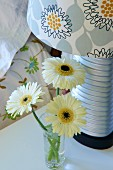 Modern bedside lamp with floral lampshade next to small vase of gerbera daisies