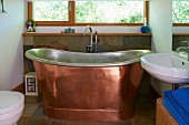 Free-standing copper bathtub in modern bathroom