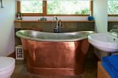 Free-standing copper bathtub in modern bathroom