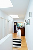 Bright hallway with black and white rug and antique grandfather clock