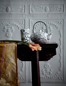 Black and white, patterned, china teapot and tea bowls on dark console table against white wall with floral reliefs