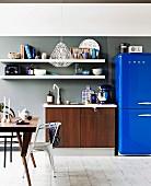 White shelves above wood-effect sink unit next to bright blue fridge