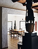 African sculpture on pedestal in front of wide open doorway with view of dining area beyond in modern house with wood-beamed ceiling
