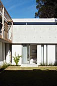 Garden facade of modern residential house in mixture of materials with exposed concrete, white-painted wall and natural wood; view in through open bedroom window