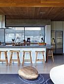 Puristische Küche mit rustikalen Holzhockern an der Frühstückstheke; Kunstobjekt aus einem Holzblock auf dem Schieferboden