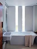 Elegant minimalistisches Bad mit Edelholztür und Lichtschlitzen hinter der freistehenden Designerwanne