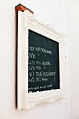 Notes on wall-mounted chalkboard with white, ornate frame