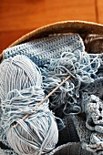 Pale blue crochet work, ball of wool and crochet needle in knitting basket