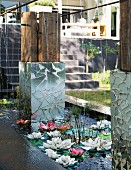 Artificial water lilies and objets d'art in pool at foot of steps leading to residential house