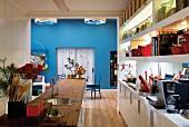 Blick über Theke und Küchenzeile mit rustikaler Arbeitsplatte in offener Küche vor blau getöntem Essbereich