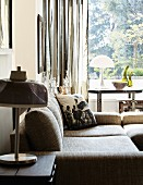 Comfortable sofa and side table with table lamp in front of window with view of garden