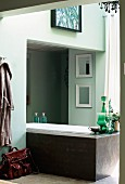 Free-standing, modern bathtub partially built into niche in bathroom painted pale green