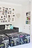 Gepolsterte Couchtische vor Sofa und Fotogalerie an der Wand