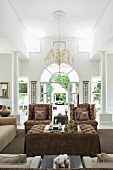 Exclusive living area with white columns, chandelier and elegant upholstered furnishings