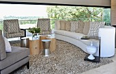 Armchairs with patterned upholstery and sofa in front of panoramic window