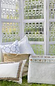 Cushions in baskets in front of carved screen in garden