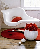 Sitting room detail with distressed walls, and a white moulded plastic chair on a round, red rug.