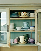 Close up of glass fronted cabinet with assortment of cups and saucers