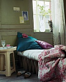 Glass of water on bedside table next to single campstyle bed with cat on window sill above