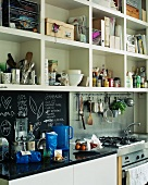 Items stored on open shelving unit above hob and sink in contemporary kitchen with chalkboard