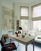 Leather armchair at wooden table in front of sofa below window with roman blinds