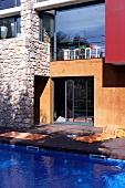 Modern house with large windows and stone walls; azure blue swimming pool with wooden terrace in foreground