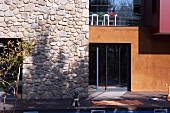 Modern facade in rustic stone and glass with large coloured planes