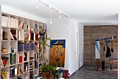 Bright room with colourful exercise equipment, modern painting and large, busy bookcase