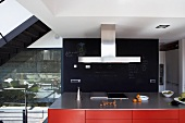 Red kitchen island in front of black slate wall panel