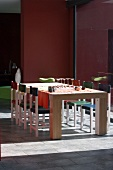 Chairs of various colours at solid wooden dining table next to floor-to-ceiling window