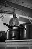 Old pans on cooker (black and white photo)