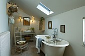 Simple attic bathroom with free-standing, antique bathtub and rush-bottomed chair with high back on terracotta tiled floor