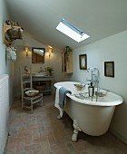 Free-standing, antique bathtub below sloping ceiling in simple bathroom of country house in northern France