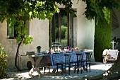 Rustikaler Holztisch mit einfachen Holzstühlen vor provenzalischem Landhaus