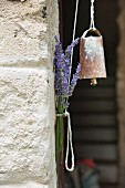 Old bell hanging from cord and bunch of lavender next to wall
